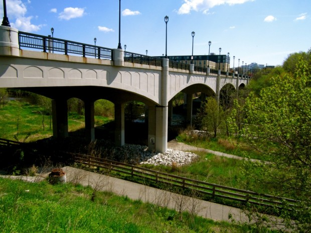 Designed and built in the early 1990s, no one has yet called the current North Avenue Bridge a masterpiece, but it does include ornamental railings and streetlights and cast concrete arches that may have been as a tribute to the arched spans of its 1920s predecessor. The river is much narrower at this point than it was historically following the opening of the North Avenue dam in the late 1990s. Carl Swanson photo