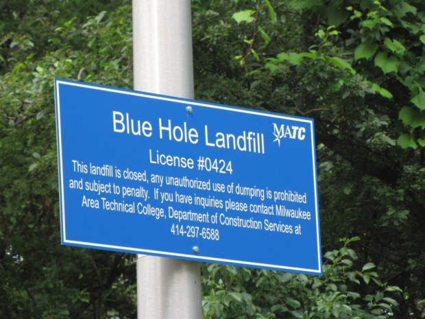The twin quarry lakes, Cement and Blue Hole, are gone. A university parking lot occupies the former Cement Lake site, and the Blue Hole name lives on only on this landfill sign. Photo by Carl Swanson