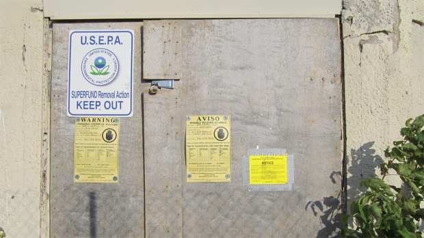 An unwelcoming entryway. In addition to being fenced off and padlocked, the door has EPA Superfund warnings in both English and Spanish. The notice at far right is a City of Milwaukee order directing the owner to demolish the property. Photo by Carl Swanson