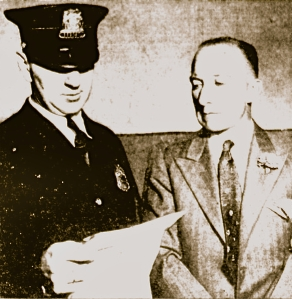 The always impeccably-dressed Capt. E.J. Bodenlos listens as a police officer reads a city citation. Milwaukee Journal photo