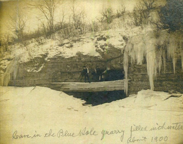 Two men, possibly not thinking clearly, stand on an ice shelf over a water-filled cave in the former quarry in 1900. Courtesy Milwaukee County Historical Society