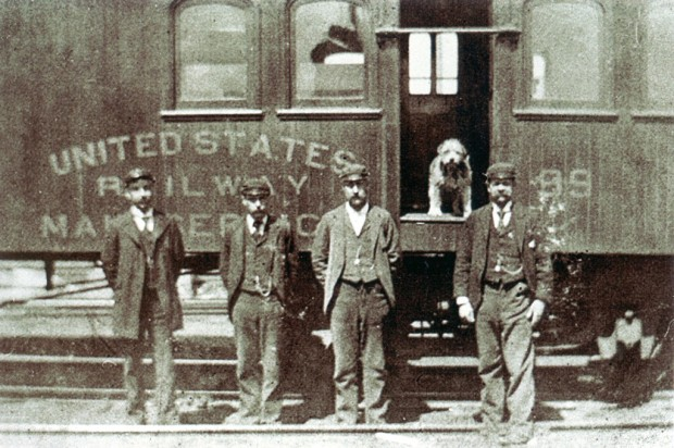 Owney stands in the doorway of a Railway Post Office car, surrounded by his postal clerk friends. Courtesy National Postal Museum