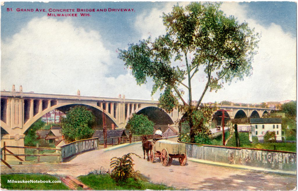 A horse cart is featured in this vintage postcard view of Milwaukee's original Grand Avenue viaduct